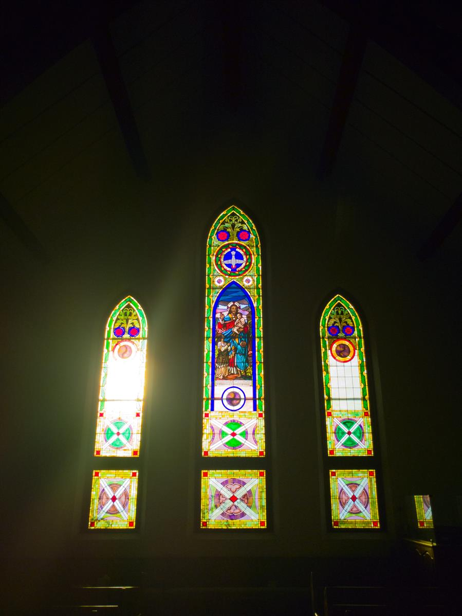 Afternoon sunlight streams through the stained glass windows at Jubilee Mennonite Church in Meridian, Mississippi.