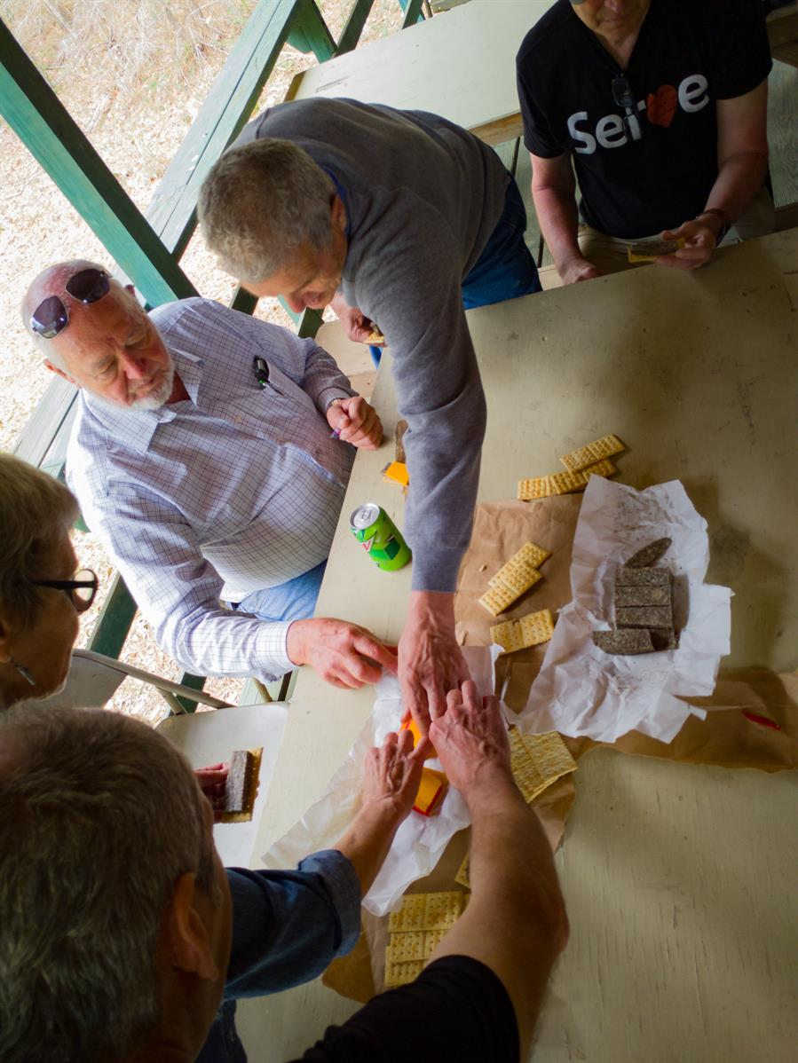 "A snack break outside Nanih Waiya Indian Mennonite Church near Preston, Mississippi, was an opportunity for Larry Miller to introduce the group to a traditional ""logger lunch"" of souse meat (head cheese), hoop cheese, and crackers. Most participants opted for just the cheese."