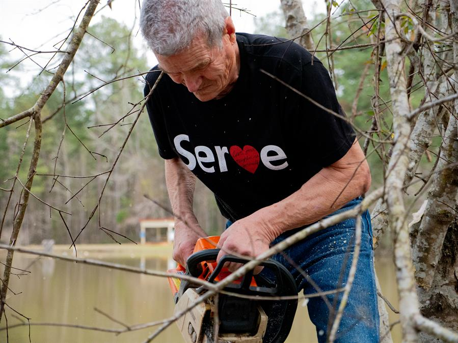 Gerald Fryenberger cuts brushwood during a workday at Pine Lake Fellowship Camp in Meridian, Mississippi.