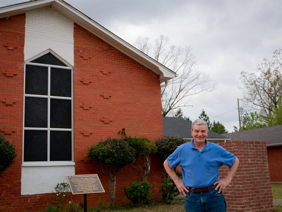 Service-learning tour participant Gerald Fryenberger stands in front of Mt. Zion United Methodist Church outside of Philadelphia, Mississippi. After the church was burned down in 1964, Fryenberger traveled to Mississippi with Mennonite Disaster Service to help in its reconstruction.
